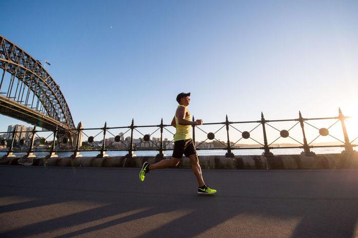 Ein Sportler löuft auf einer Brücke am Wasser einen Marathon. Im Hintergrund sieht man das Wasser und die Sonne.