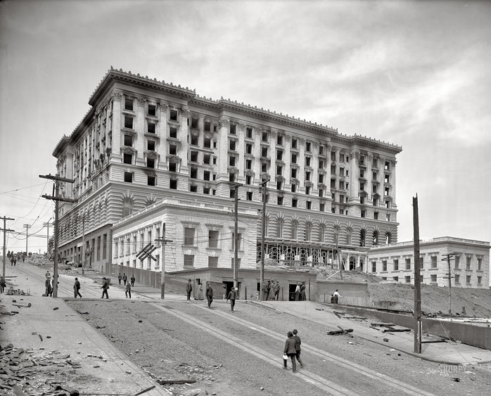 Image of the San Francisco Fairmont hotel uder construction, hotel sitting atop hill with people strolling nearby, circa 1906.