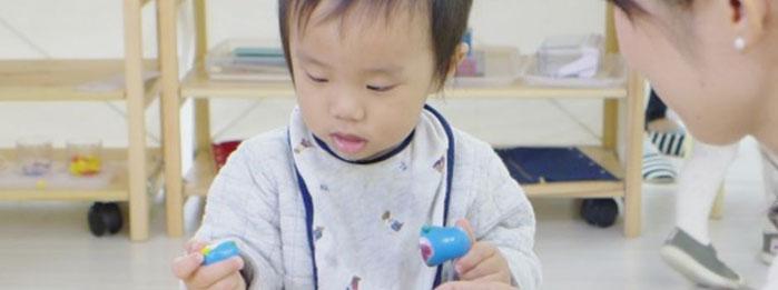 1歳の男子がモンテッソーリの活動で指を使ったおしごとをしています。