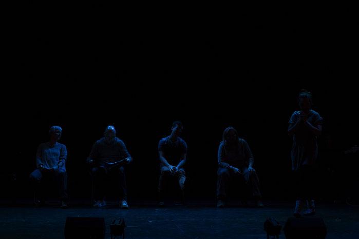 Einige Personen auf derBühne werden in schwaches blaues Licht getaucht.