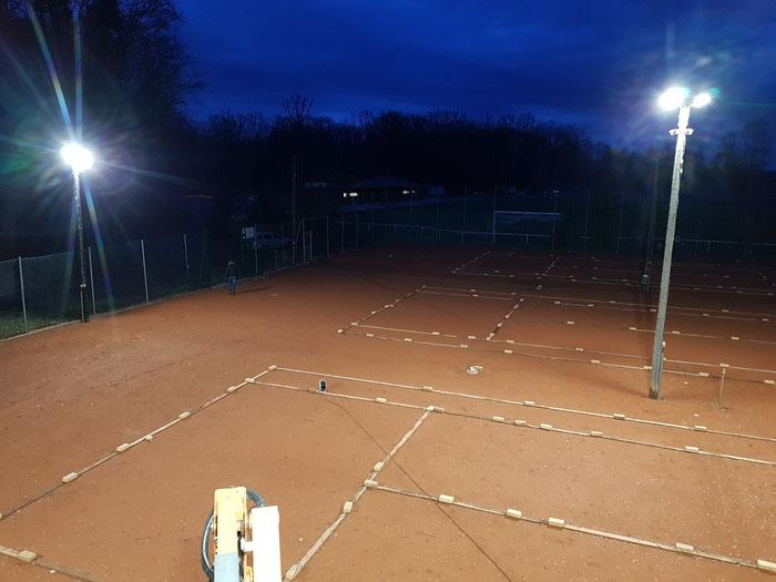 Hell erleuchtet ist der winterliche Tennisplatz