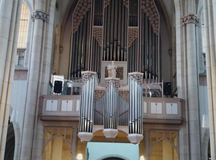 """Blick von unten auf die Orgelbühne: Man kann links und rechts die aus einem Holzgerüst und Plexiglas gebauten """"Kabinen"""" erkennen."""