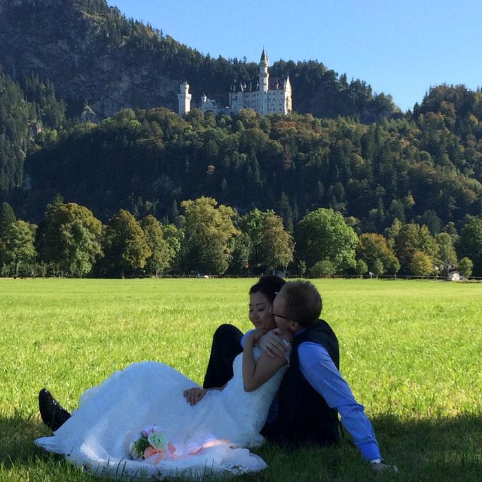 Hochzeitsfoto auf der Wiese vor Schloss Neuschwanstein