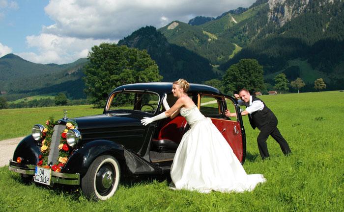 Hochzeitspaar schiebt Oldtimer im Hochzeitsservice Königswinkel
