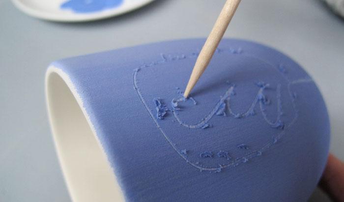 Auskratzen von Farbe auf Keramiktasse