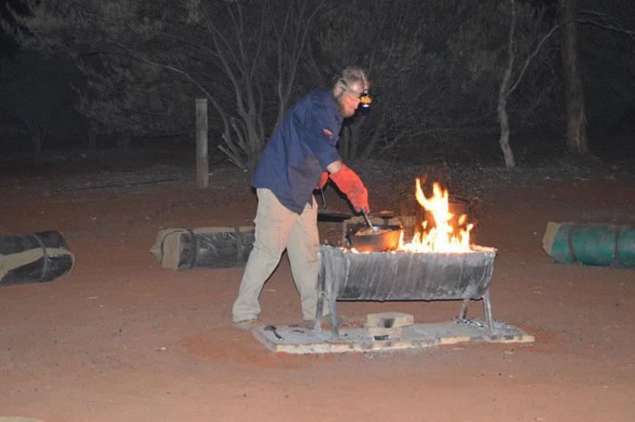 Unser Guide Nacho zaubert ein Abendessen über dem Lagerfeuer. Rundherum die noch zusammengerollten Swags.