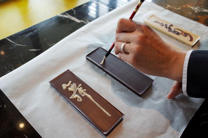 Chinesische Schriftzeichen, geschrieben mit Schokolade. Einmalige Kunstaktion für die Zotter Chocolate Factory Shanghai. Foto © Yan Zhou