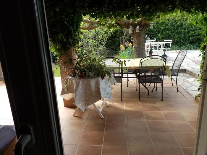Blick auf Terrasse mit Tisch und Gartenstühlen