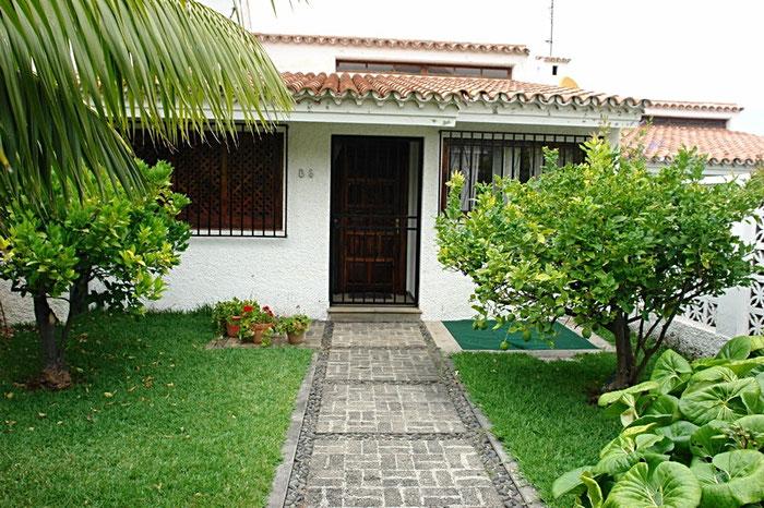 Am Eingangsbereich vom Haus sieht man rechts und links Orangenbäume und darunter Rasen.