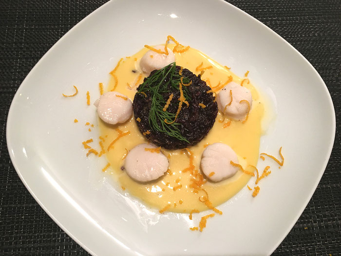 Kammmuscheln an Orangensauce mit schwarzen Reisplätzchen