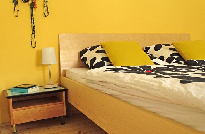 Holzbett mit Nachtkästchen