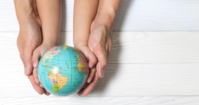 Parent and child's hands holding a small globe