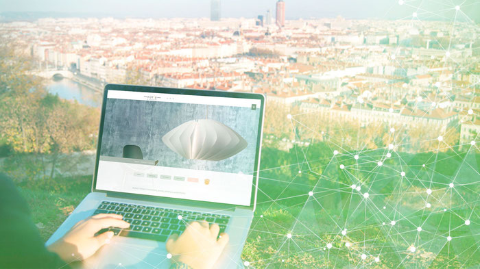 Un usuario de Jimdo trabaja en su web con la ciudad de Barcelona como fondo.
