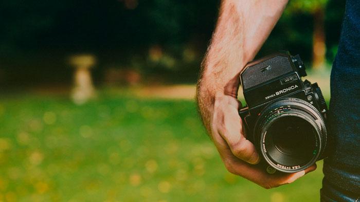 Un hombre sostiene una cámara fotográfica.