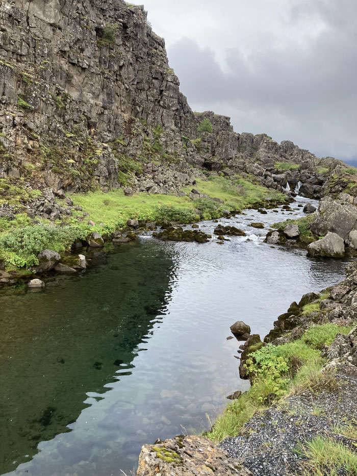 The crystal clear Icelandic waters of the Oxara River flowing past Almannagja.