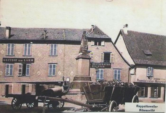 """Place de la Sinne à Ribeauvillé, sur la droite affiche annonçant ne commercialiser que des """"Rappoltsweiler Naturwein"""" c'est à dire des """"vins nature"""" de Ribeauvillé - Photographie : Cercle de recherches historiques de Ribeauvillé et environs, revue N°22"""