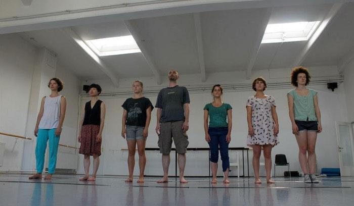 Sieben junge Performer stehen in einer Reihe im Tanzstudio.