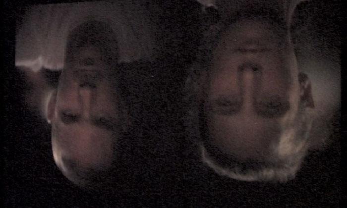 Eine dunkle Projektion zweier Gesichter.