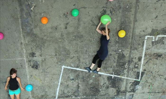 Zwei Frauen, die sich auf dem Boden liegend bunte Luftballons zuwerfen.