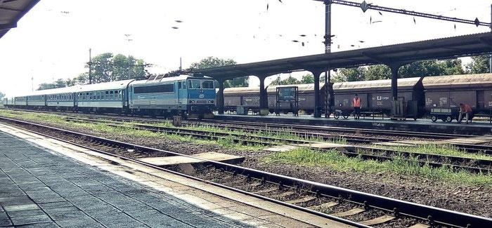 Einfahrt eines Schnellzuges, am Bahnsteig wartet die Mitarbeiterin mit dem Postwagen