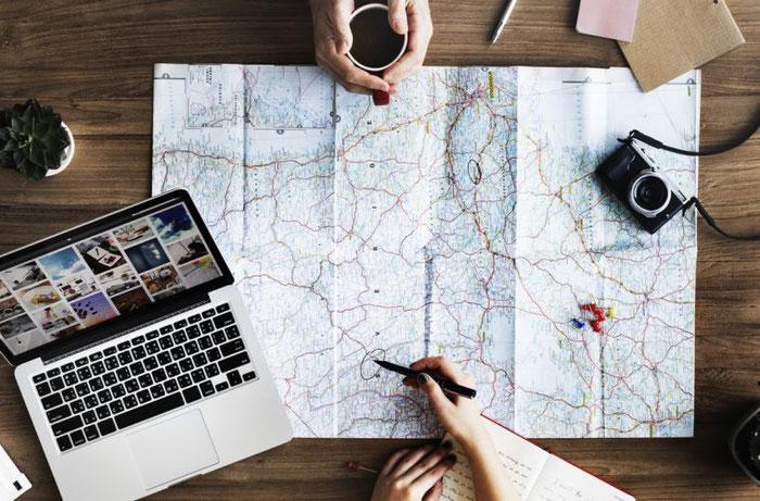 Vue d'en haut d'une table avec un plan déplié, un ordinateur portable, un appareil photo, une plante, des mains autour d'une tasse de café et des mains tenant un stylo