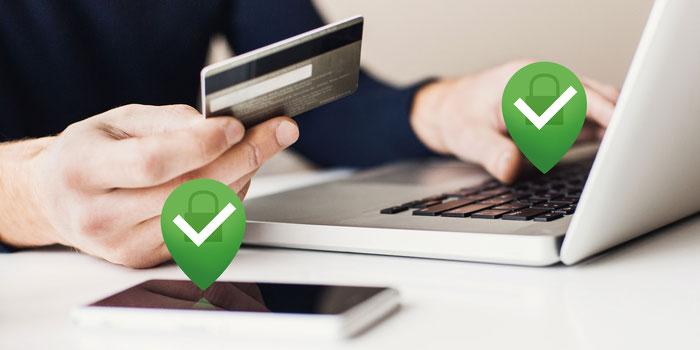 Mains tenant une carte de crédit et tapant à l'ordinateur, téléphone portable en premier plan et deux icônes vertes de sécurité