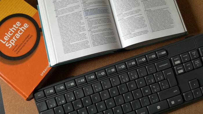 Foto mit Tastatur, Leichte-Sprache-Ratgeber und einem aufgeschlagenen Wörterbuch