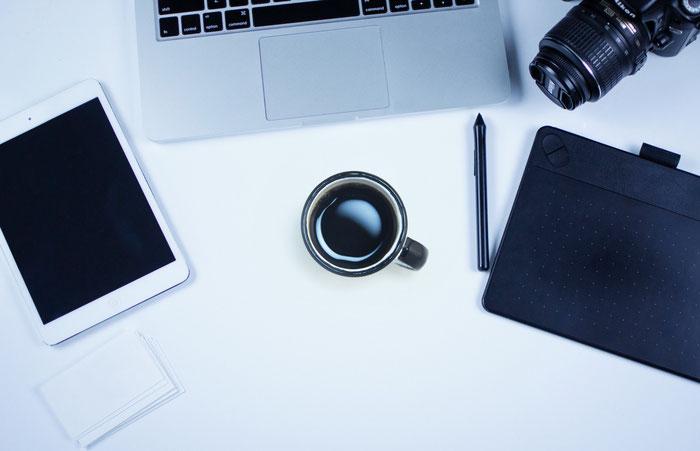 iPadやスマートタブレット、コーヒー、一眼レフが置かれたおしゃれなデスク