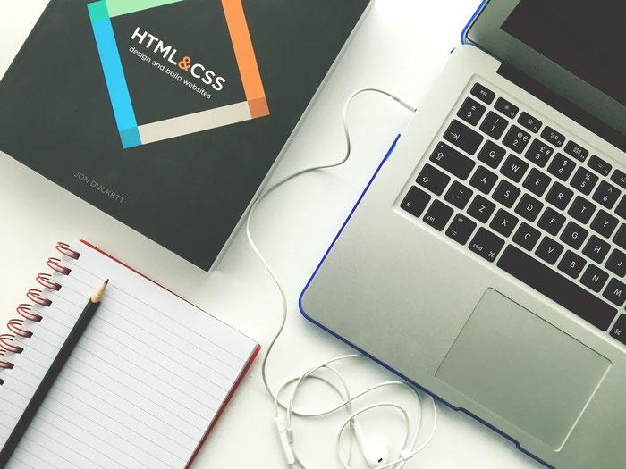 パソコンとノートとCSSの参考本の画像