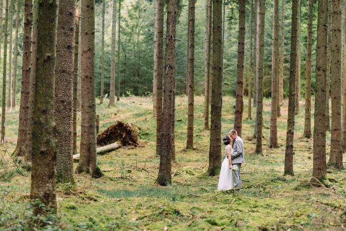 Das Brautpaar teilt einen innigen Kuss im idyllischen Wald