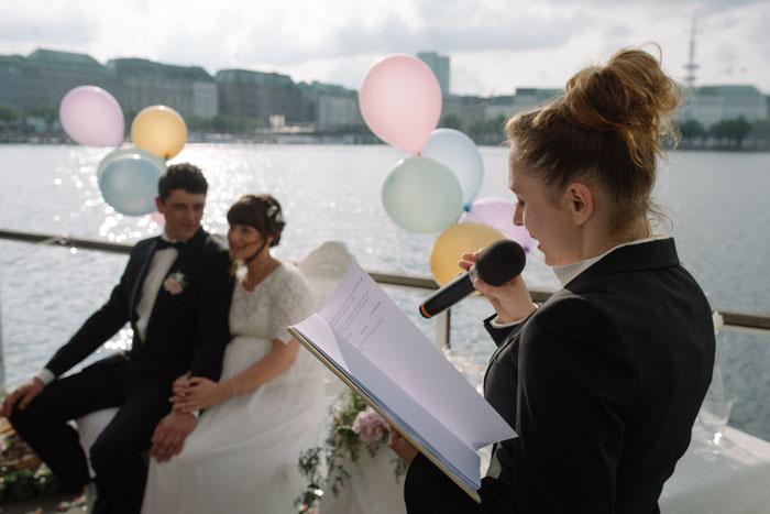 Hochzeitsrednerin Constanze mit Brautpaar auf einem Boot. Alle sind festlich gekleidet. An der Reling sind bunte Luftballons