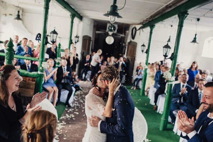 Die Brautleute küssen sich. Von oben fällt Konfetti. Die Gäste sind seitlich von ihnen, amüsieren sich und applaudieren