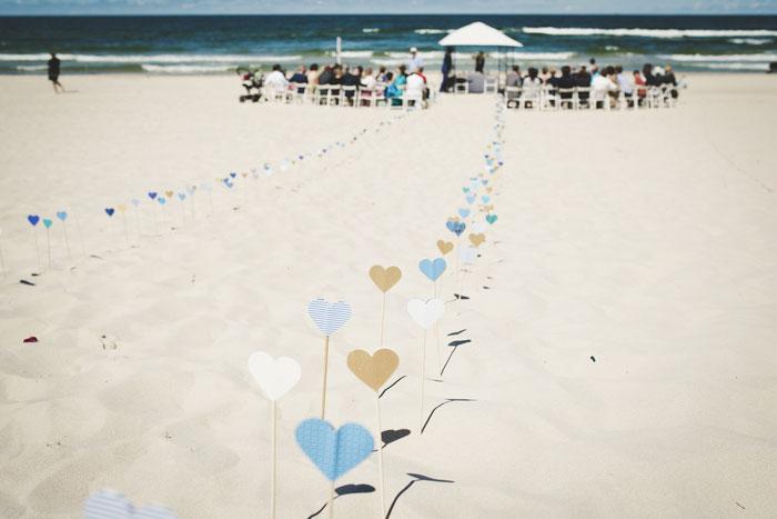 Bunte Papier-Herzchen markieren im Sand den Weg zum Altar, die Hochzeitsgemeinde und das Meer im Hintergrund