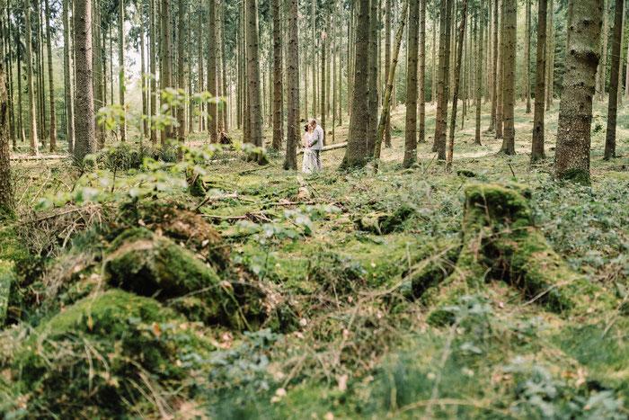 Ein Traupaar in unweiter Ferne im Wald, Moos im Vordergrund des Bildes