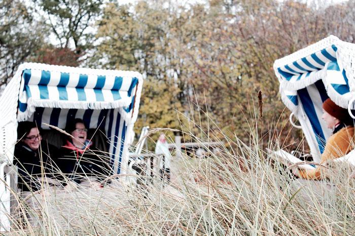 Brautpaar und Hochzeitsrednerin Constanze sitzen lachend in ihren Strandkörben