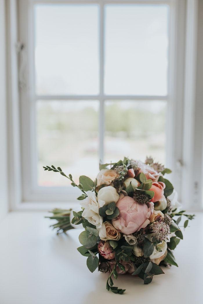 Bouquet verschiedener Blumen vor einem Fenster mit weißem Rahmen