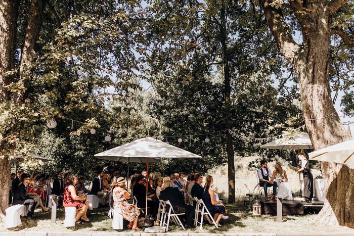 Die Hochzeitsgesellschaft sitzt auf Stühlen. Weiße Sonnenschirme und Bäume spenden Schatten
