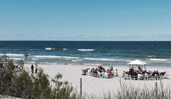 Hochzeitsgemeinde am Strand, das Meer reicht bis zum Horizont, ein kleiner Pavillon schützt das Brautpaar vor der Sonne