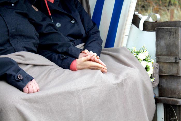 Ein Paar sitzt händestreichelnd im Strandkorb mit einer Decke. Seitlich liegt ein Strauß Blumen
