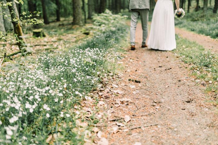 Hochzeitspaar läuft auf einem Waldweg, Blumen wachsen am Wegesrand