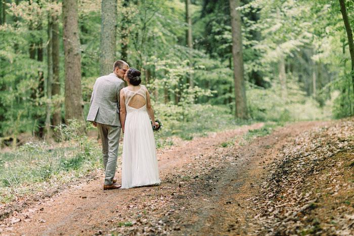 Brautleute küssen sich auf einem erdigen Weg im Wald. Sie trägt den Brautstrauß in der Hand