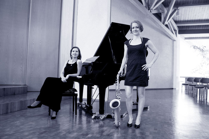 Zwei elegant gekleidete Musikerinnen mit Flügel und Saxophon