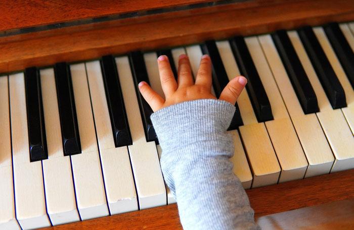 Kleine Kinderhand auf der Klaviertastur