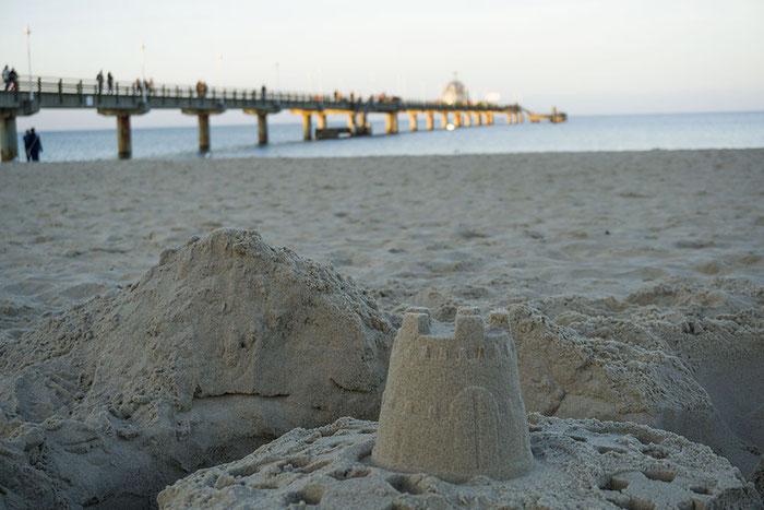 Beim Sonnenuntergang Sandburg bauen mit Kindern am Strand vom Zinnowitz