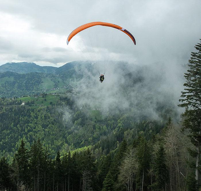Mit dem Gleitschirm in Richtung Genfer See. Von den bewaldeten Berghängen steigt Nebel auf. Foto: Klaus Schoerner