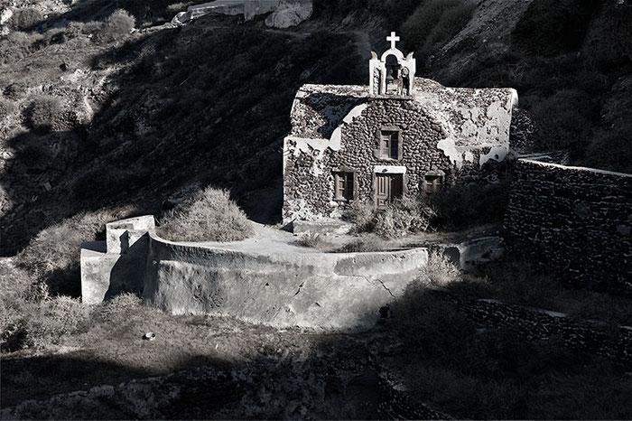 Die kleine Kapelle in den Felsen oberhalb von Ammoudi Harbour in den ersten Sonnenstrahlen der über den Kraterrand aufsteigenden Sonne. Leica M9 mit 90er Elmarit. Foto: Klaus Schoerner
