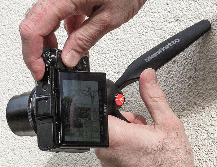 Eine Hand drückt das Stativ an die Wand, die andere Hand bedient die Kamera. Foto. Klaus Schoerner