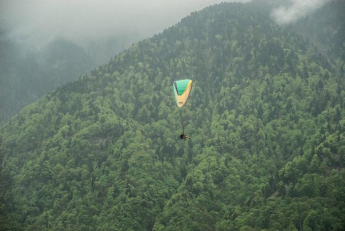 Mit dem Gleitschirm in Richtung Genfer See. Über den bewaldeten Berghängen liegt Dunst. Foto: Klaus Schoerner
