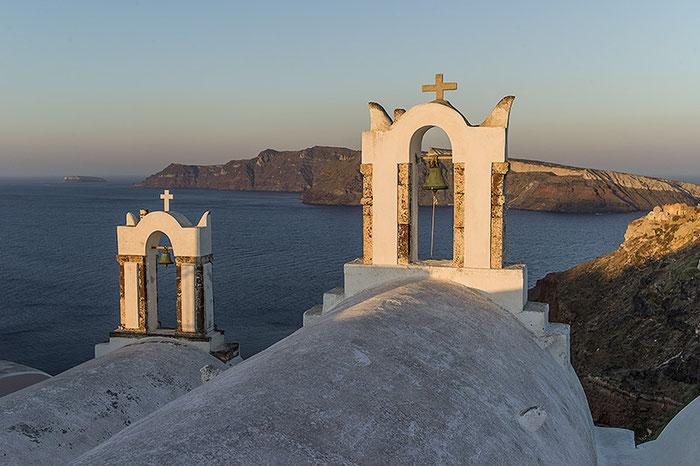 Bei Sonnenaufgang fallen die ersten Sonnenstrahlen auf die Kapellen von Oia und die Nachbarinsel Thirassia im Hintergrund.Leica M9 mit 35er Biogon ZM. Foto: Klaus Schoerner