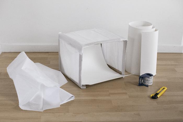 Caja de cartón forrada con papel tisú y cartulina blanca como fondo